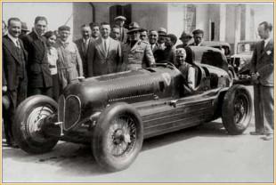 """La prima volta del Cavallino. La """"Bimotore"""", appena ultimata, in posa con Nuvolari al volante ed Enzo Ferrari sorridente, davanti alla scuderia. L'auto non ha emblema. Ferrari porrà, anche sulla calandra, il suo Cavallino al posto del Biscione, suscitando le proteste dell'Alfa Romeo"""