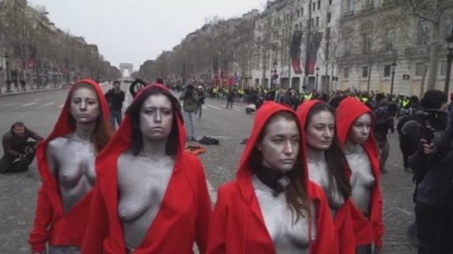 Vestite da Marianna, simbolo della Repubblica francese, tre ragazze - immobili e a seno nudo nonostante il gelo - sono rimaste una buona mezz'ora oggi, impassibili, davanti agli scudi della polizia che bloccava i gilet gialli nel mezzo degli Champs-Elysees.     Anche se qualcuno ha inizialmente pensato potesse trattarsi delle Femen, celebri per le loro dimostrazioni di protesta, i media francesi hanno spiegato che si trattava di una performance artistica della franco-lussemburghese Deborah de Robertis, nota per essersi spogliata in diversi musei francesi.