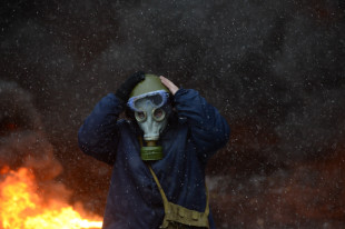 Protester wearing a tear gas mask against background of the mass